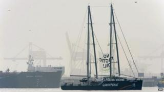 """A banner reading """"No Arctic oil!"""" hangs from Greenpeace's Rainbow Warrior docked next to the Russian oil tanker Mikhail Ulyanov (L) at the harbour of Rotterdam"""