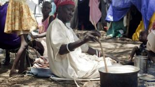 A South Sudanese woman displaced by recent fighting prepares a meal at the Bor camp for the internally displaced in Bor town, Jonglei state, 29 April 2014