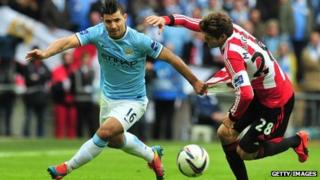 Manchester City's Argentinian striker Sergio Aguero goes past a defender
