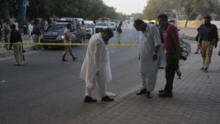 Pakistani investigators work at the scene after the attack on prominent Pakistani journalist Hamid Mir in Karachi on April 19, 2014.