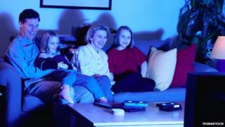 Family on a sofa watching television