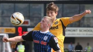 Rochdale's Jamie Allen is challenged for the high bouncing ball by Newport County's Max Porter