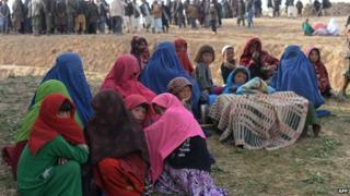 Landslide-affected Afghan villagers look on as they await donated relief supplies at the scene of the incident in Argo district in Badakhshan on May 4, 2014