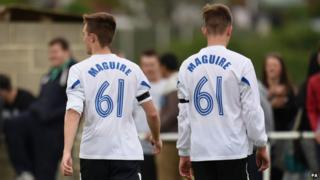 """Two players in """"Maguire"""" shirts"""