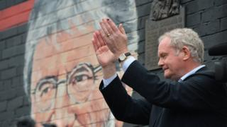 Martin McGuinness in front of Gerry Adams mural