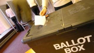 Woman casting vote in ballot box