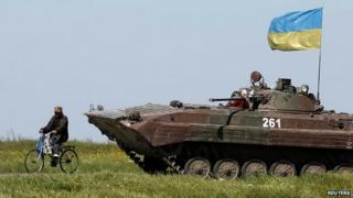 A man rides a bike past a Ukrainian armoured vehicle at a checkpoint in Mariupol - 7 May 2014