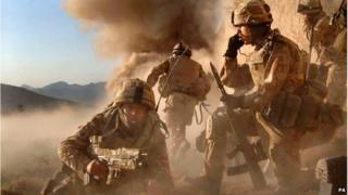 Soldiers in uniform in Afghanistan. Smoke is rising in the background