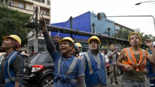 Workers look on after a strong earthquake in Mexico City on 8 May 2014.