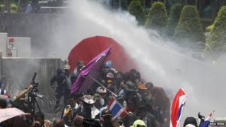 Police fire teargas and water cannon at anti-government protesters at a police compound housing a government security group in the north of Bangkok on 9 May.