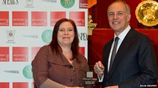 Gaby Rivers, curator of The Judge's Lodging, receives the award from Loyd Grossman