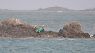St John inshore rescue boat crew with dinghy off Bordeaux, Guernsey