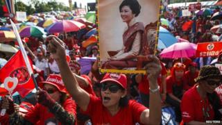 """A member of the pro-government """"red shirt"""" group holds a picture of ousted Thai prime minister Yingluck Shinawatra during a rally in Nakhon Pathom province on the outskirts of Bangkok, May 10"""