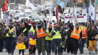 "Members of the ""Omushkegowuk Walkers"" and their supporters march towards Parliament Hill 24 February 2014"
