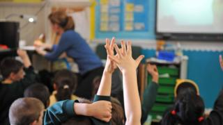 children with their hands up in a classroom