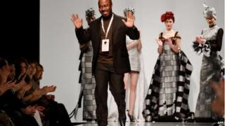 Ghanaian designer Kofi Ansah salutes at the end of his show in Rome, February 2009