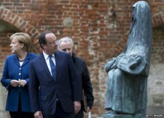 French President Francois Hollande looks at a sculpture as he visits the St John Convent in Stralsund, north-eastern Germany with German Chancellor Angela Merkel