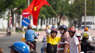 Protesters stand on the corner of a street in Quan Doan 4, Binh Duong province, near Song Than 2 Industrial Park in Vietnam, on 14 May.