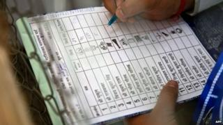 An Indian polling agent notes down the numbers of votes after an Electronic Voting Machine (EVM) was opened by election officials at a counting centre in Ghaziabad on May 16, 2014.