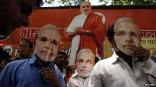 "Supporters of Hindu nationalist Narendra Modi, prime ministerial candidate for India""s main opposition Bharatiya Janata Party (BJP), wear masks depicting Modi outside their party office in Mumbai"