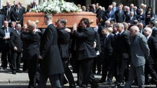 Mourners carry the coffin of Hugh Smyth