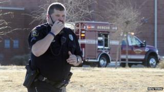 A Roswell police officer responds as law enforcement personnel set up a perimeter following an early morning shooting at Berrendo Middle School in Roswell, New Mexico 14 January 2014