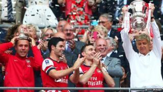Arsene Wenger lifts a trophy in celebration alongside Lukas Podolski, Mikel Arteta and Thomas Vermaelen