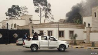 Armed men aim their weapons from a vehicle as smoke rises in the background near the General National Congress in Tripoli 18 May