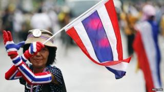 An anti-government protester marching in the city centre celebrates shortly after a Thai court delivered its verdict on Prime Minister Yingluck Shinawatra, in Bangkok, 7 May 2014