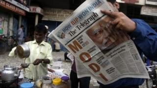 A man reads a newspaper with opposition leader Narendra Modi featured in the headlines.