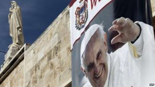 A banner showing a picture of Pope Francis is displayed from the wall of the Church of St Catherine, which adjoins the Church of the Nativity (18 May 2014)