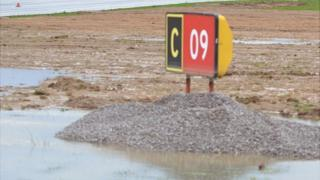 Runway sign surrounded by water