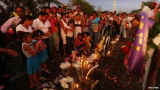 Relatives and residents light candles as they pay respect at the site of a bus accident in Fundacion, northern Colombia, May 19, 2014