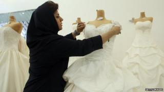 A woman adjusts a wedding dress in Tehran, Iran