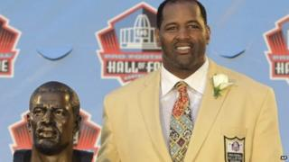 Richard Dent poses with a bust of himself during induction ceremonies at the Pro Football Hall of Fame in Canton, Ohio 6 August 2011