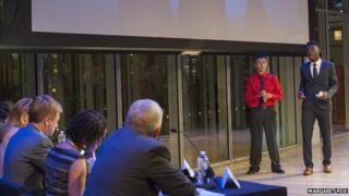 Two boys give a presentation in front of judges