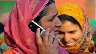 A Kashmiri woman speaks on her mobile phone