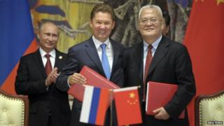 Gazprom CEO Alexei Miller and CNPC Chairman Zhou shake hands with Russian President Putin