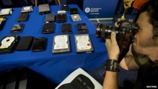 A photographer takes photo of seized hard drives that contain child pornography following a news conference to announce the arrest of 71 individuals for sharing child pornography online in New York 21 May 2014