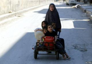 A girl pushes four children on a cart in the al-Shaar neighbourhood of Aleppo - 14 May 2014