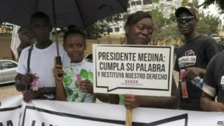 "Dominicans of Haitian descent rally in front of Dominican National Palace holding a sign that reads in Spanish ""President Medina, stand by your word and reinstate our right"" in Santo Domingo on 8 May, 2014"