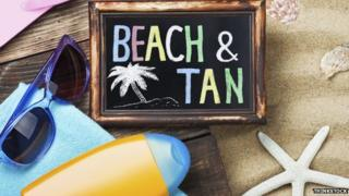 "A sign on the beach saying ""Beach & Tan"""