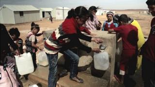 Children at a water pump in Azraq camp