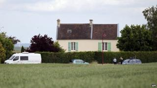 French gendarmes stand in front of a house where the mayor of Bretteville-le-Rabet was found dead