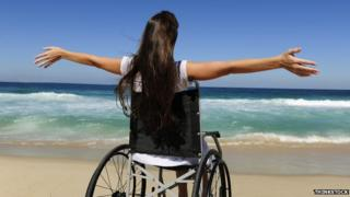 Woman in wheelchair on beach