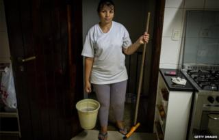 A maid in Brazil with a mop