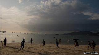People playing frisby on a beach