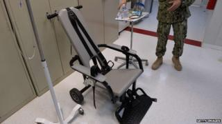 """This photo reviewed by the US military and made during an escorted visit shows a US naval medic explaining the """"feeding chair"""" procedures at the detention facility in Guantanamo Bay, Cuba 9 April 2014"""
