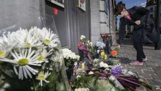 Woman lays flowers at the Jewish Museum in Brussels (25 May)