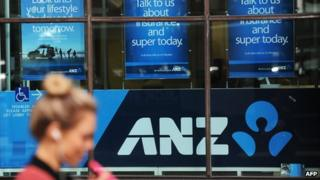 Woman walks past ANZ signage